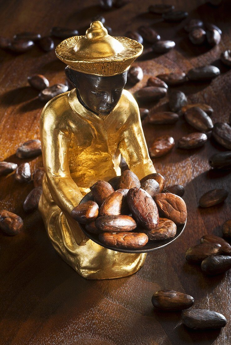 Gilded statuette holding and surrounded by cocoa beans