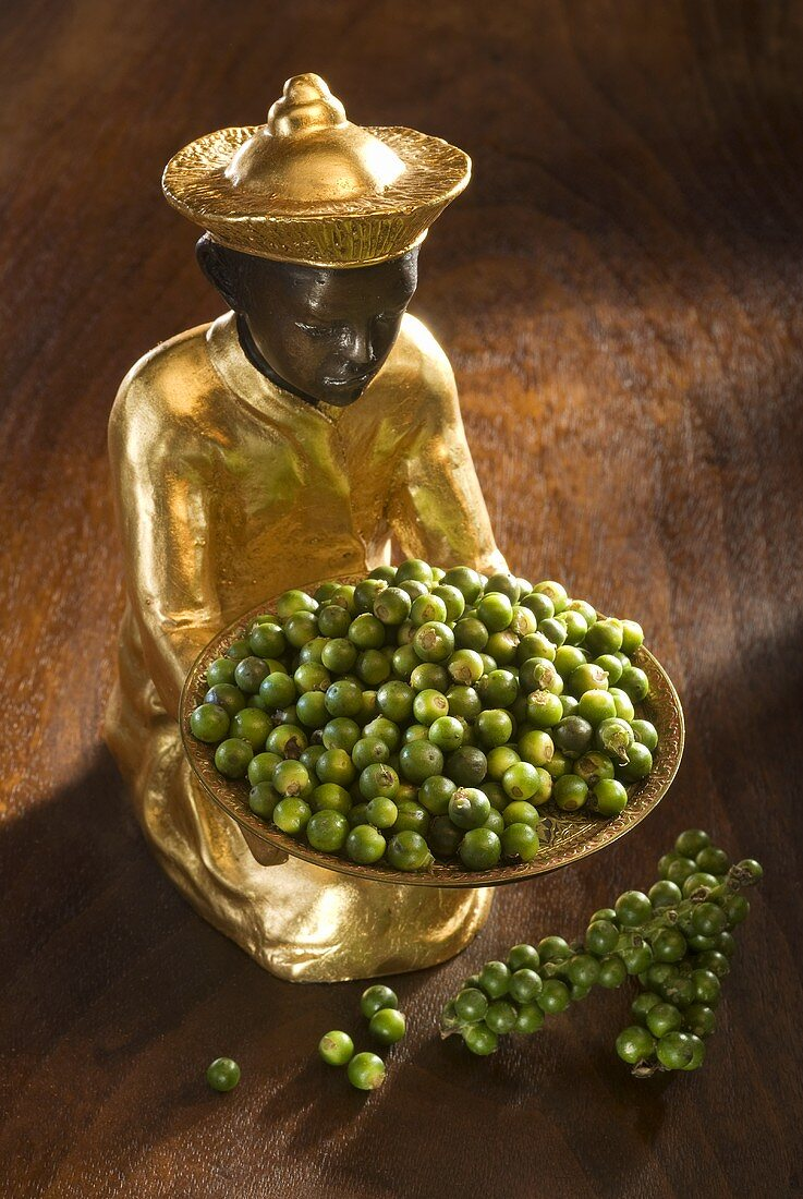 Gilded statuette with fresh green peppercorns
