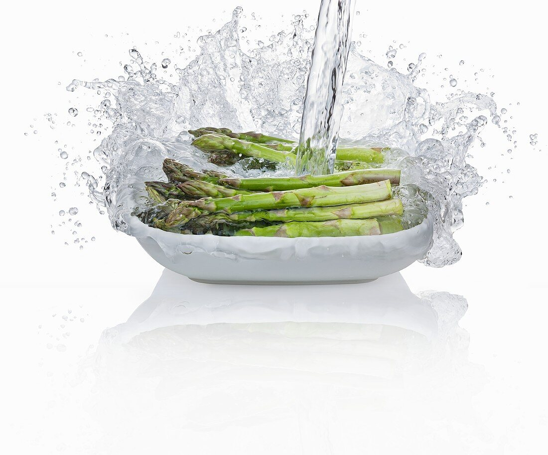 Pouring water onto green asparagus