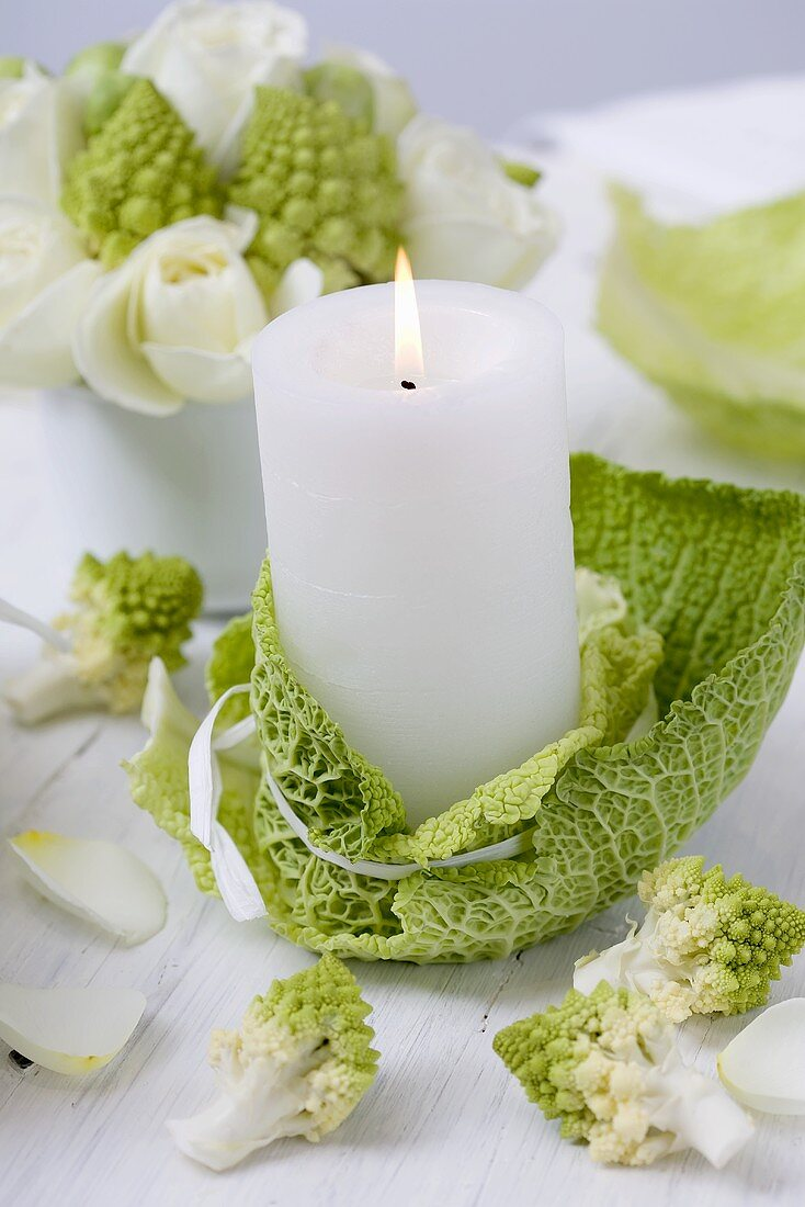Winter table decoration: candle, savoy cabbage and romanesco