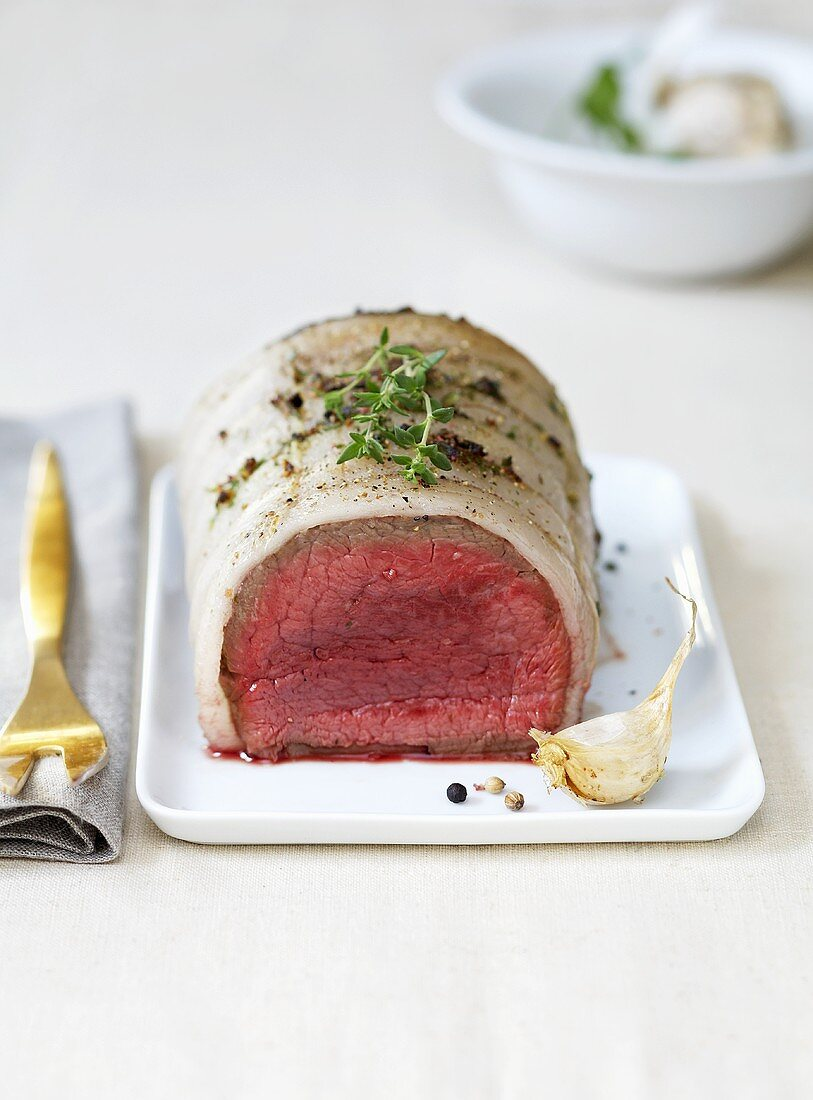 Rolled roast beef wrapped in pork fat