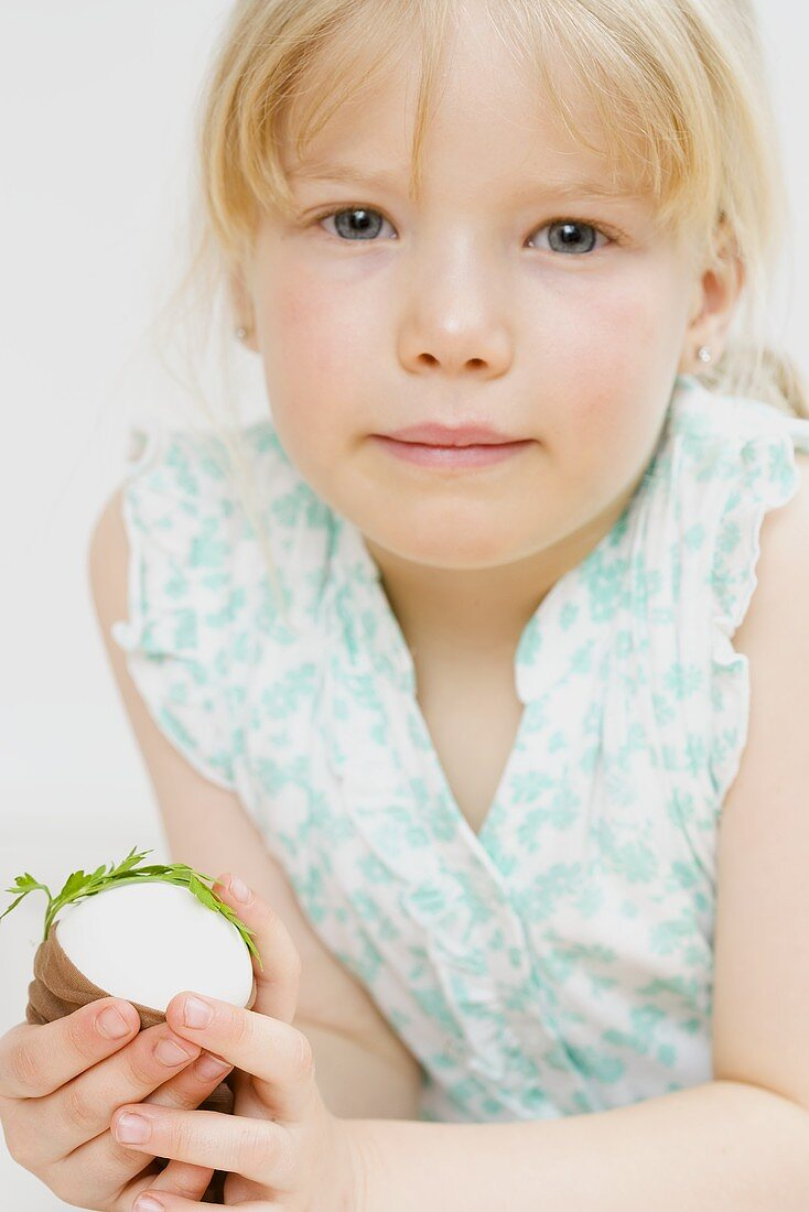 Little girl holding egg with parsley & stocking (for dyeing)