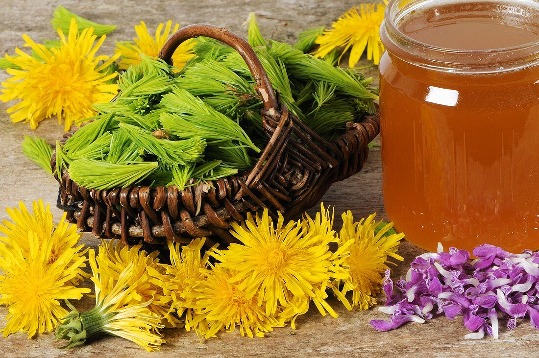 A jar of honey with spruce tips and various flowers