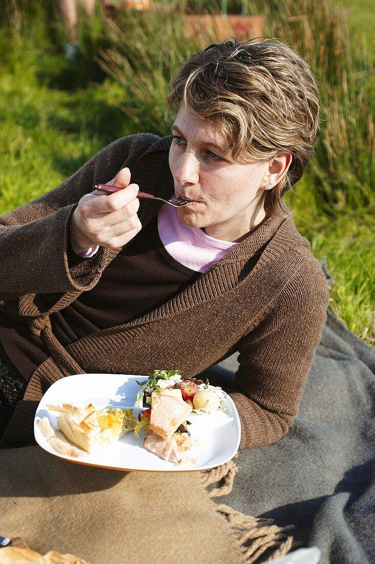 Woman lying on a picnic rug, eating
