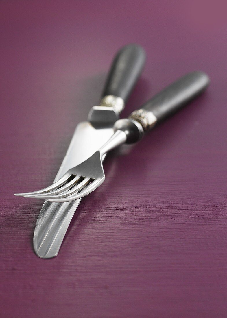 Knife & fork with wooden handles on purple wooden background