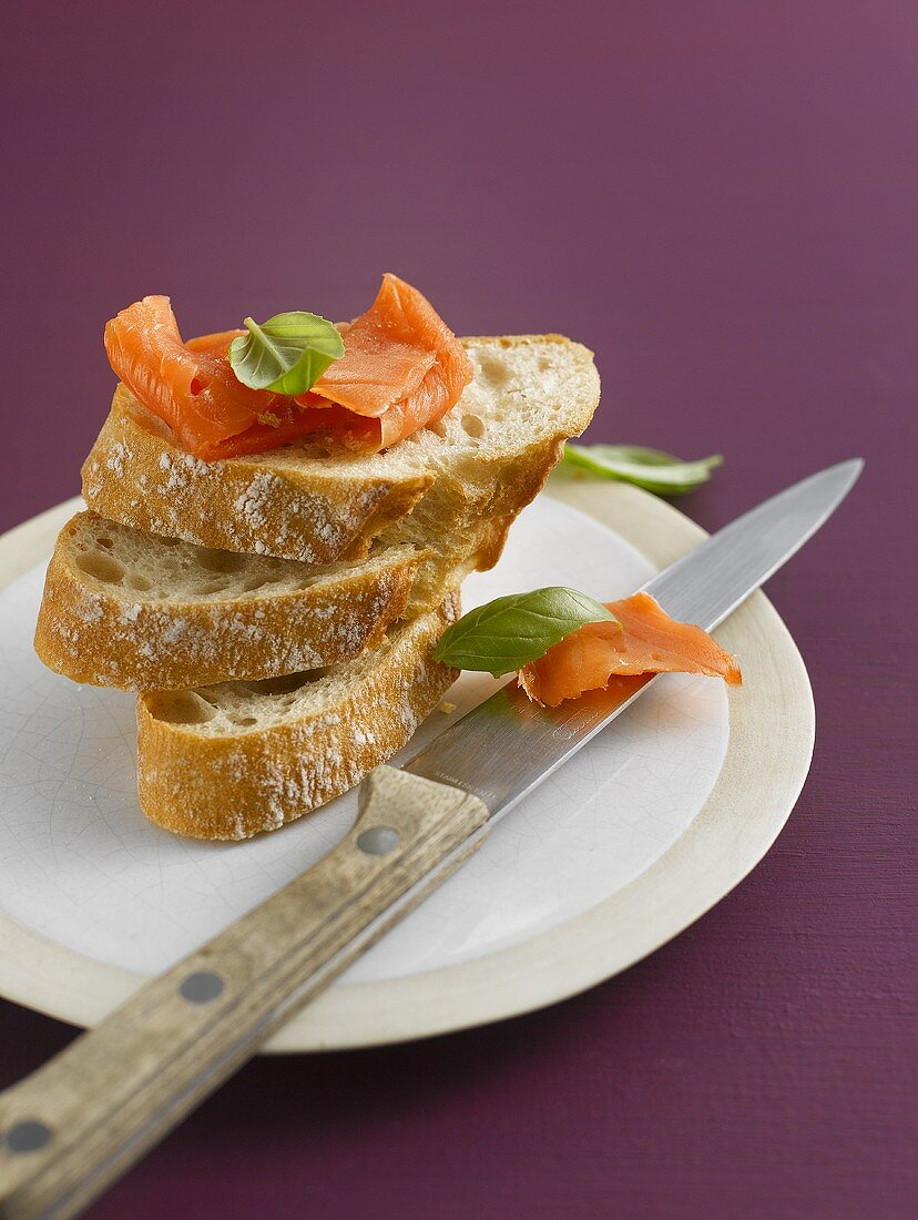 Three slices of baguette with smoked salmon and basil