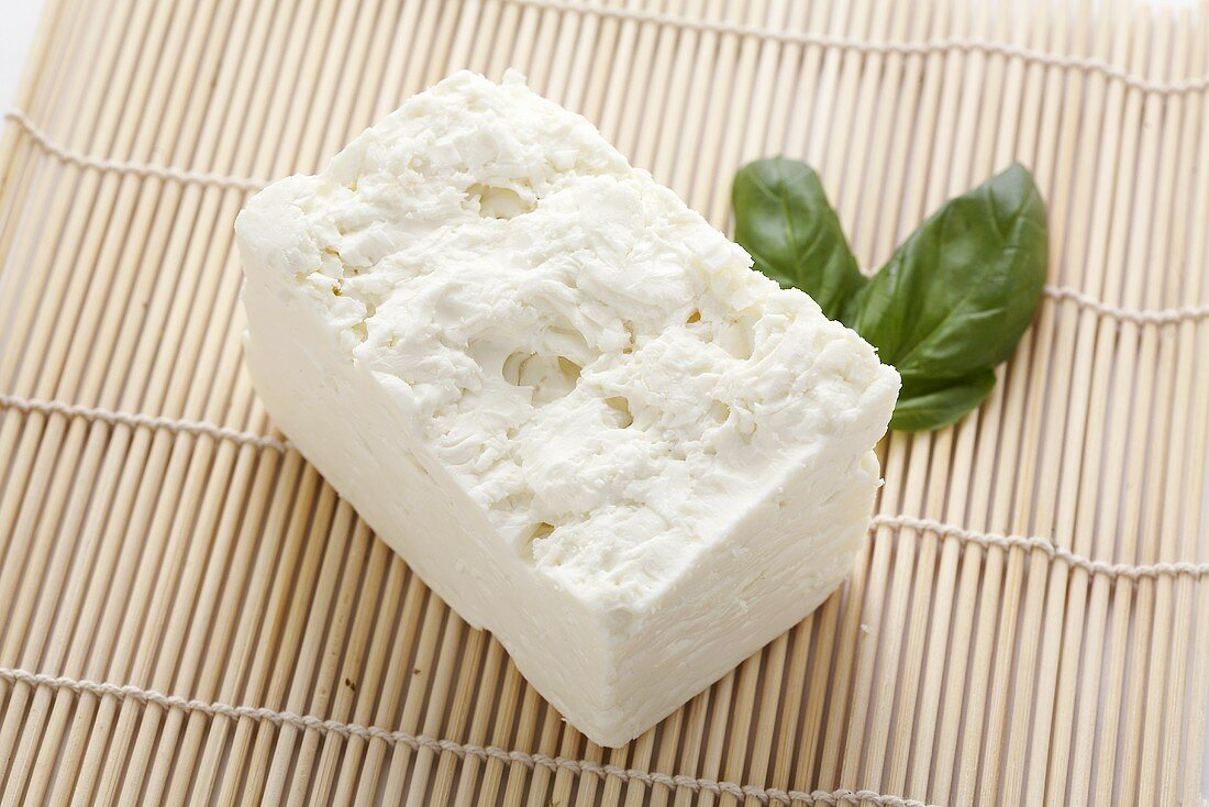 A piece of feta cheese with basil leaves