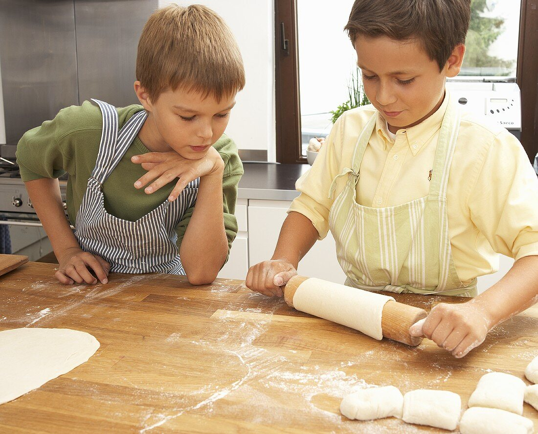 Two boys rolling out pizza dough