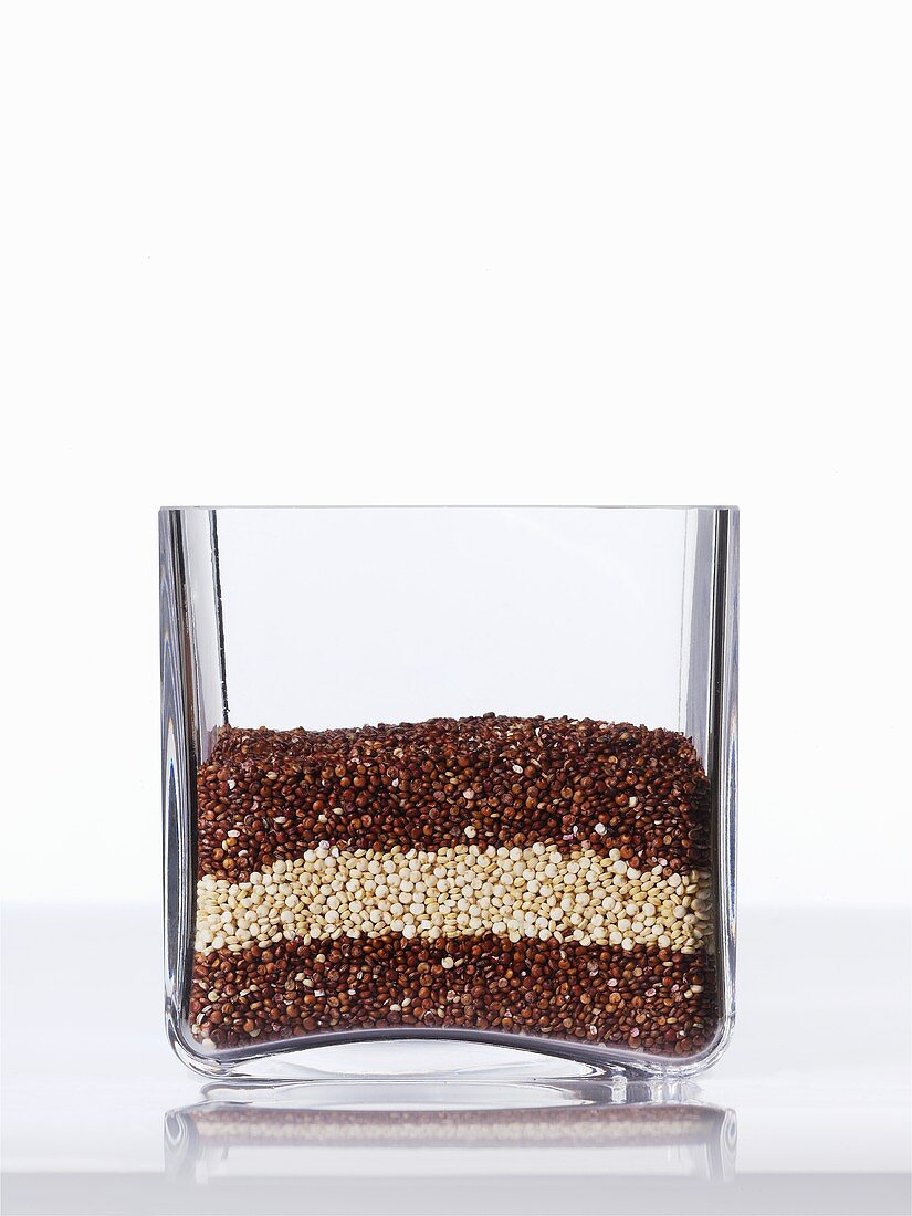 Red and white quinoa in a square glass