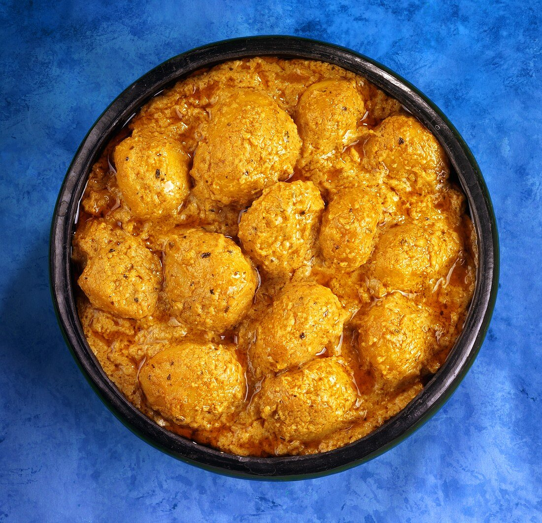 Potato balls stuffed with dried fruit in curry sauce