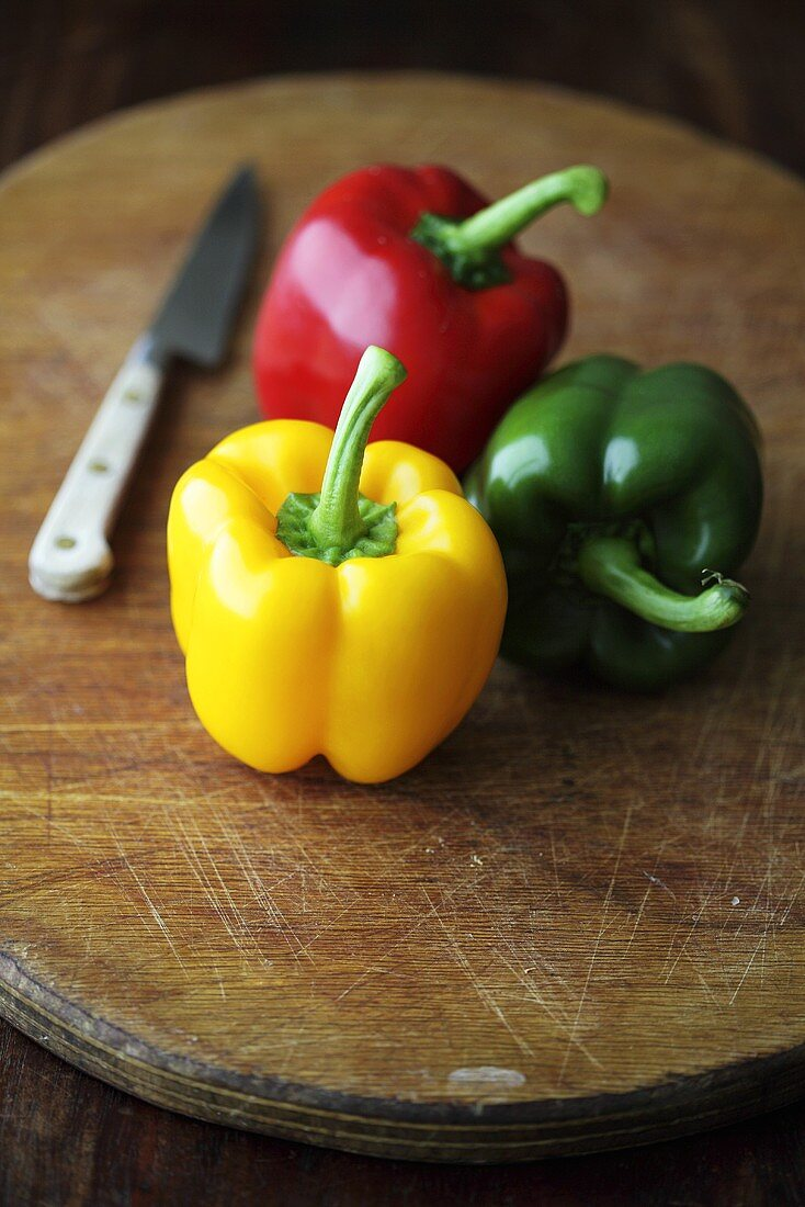 Yellow, red and green peppers on chopping board