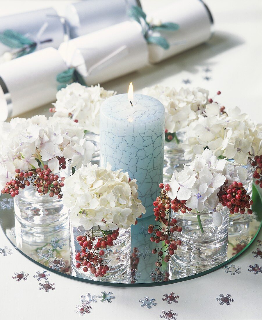 Blue candle and glasses of flowers and berries on mirror