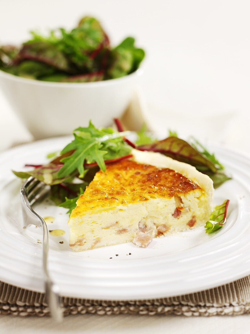 A piece of cheese and bacon quiche with side salad