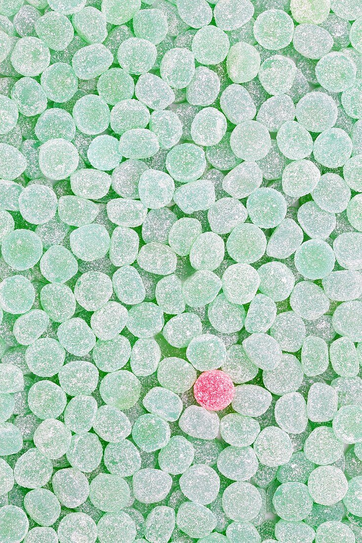One pink jelly tot surrounded by green ones