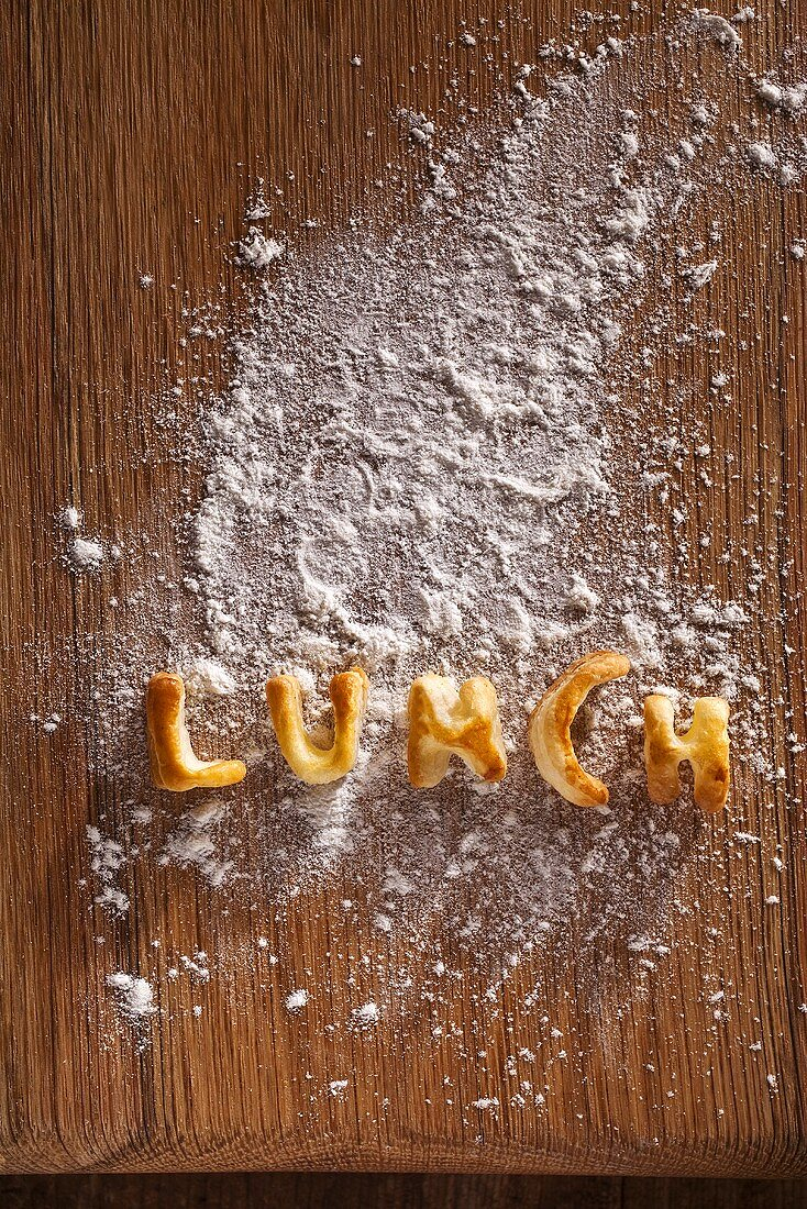 The word 'LUNCH' made out of pastry on a floured wooden board