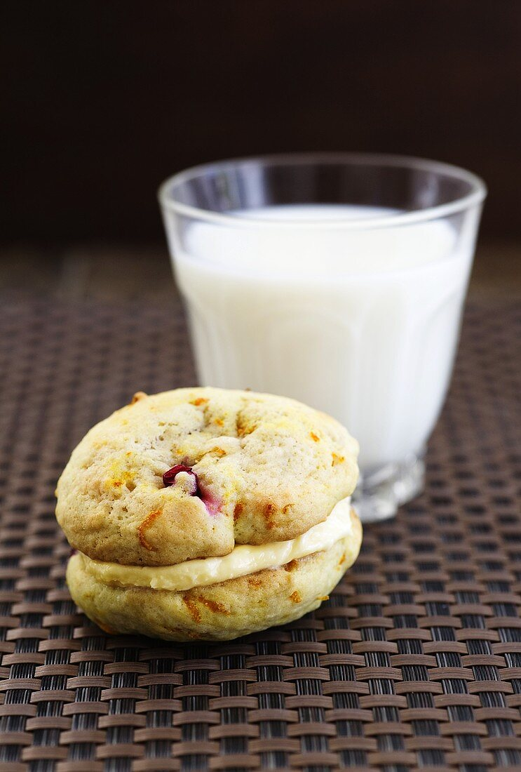 Cranberry-orange Whoopie Pies, filled with orange-vanilla cream in front of a glass of milk