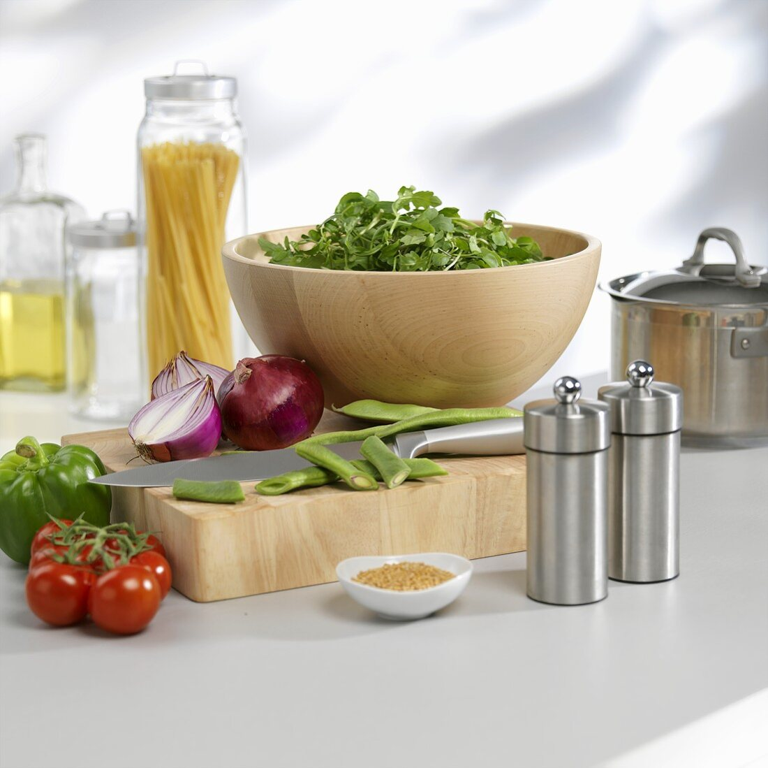 An arrangement of vegetables on a chopping board and a salad in a wooden bowl