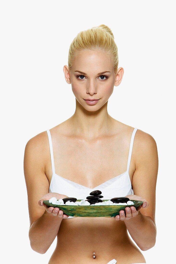 Woman holding dish of massage stones