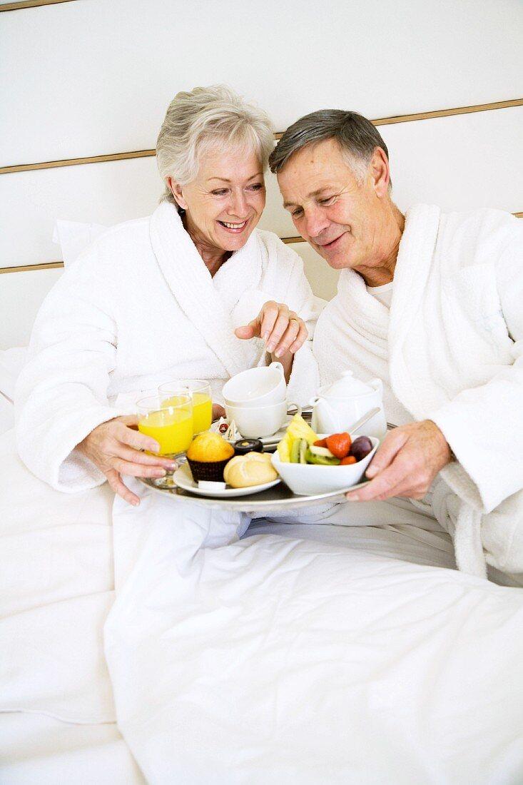 Older couple eating breakfast in bed