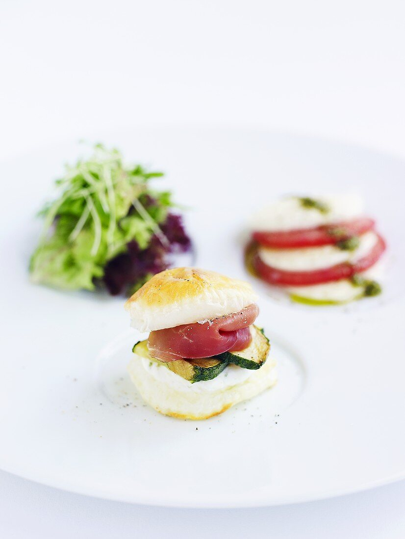 A courgette and ham roll with a side salad and tomato and mozzarella