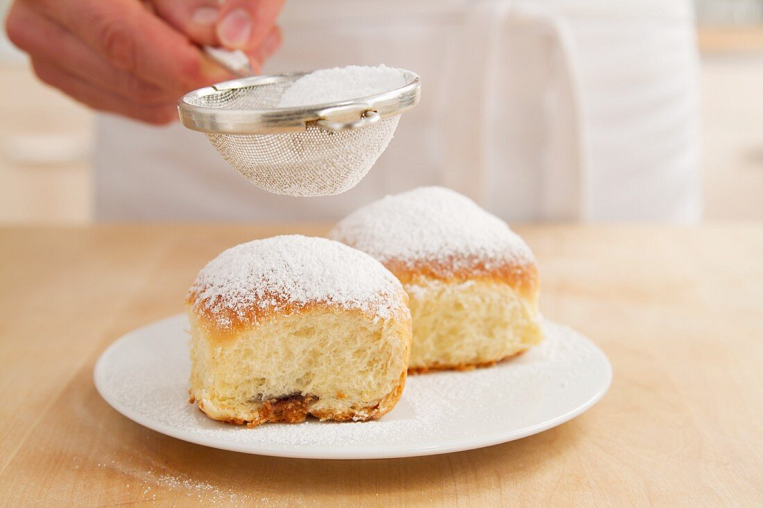 Buchteln (baked, sweet yeast dumpling) being dusted with icing sugar