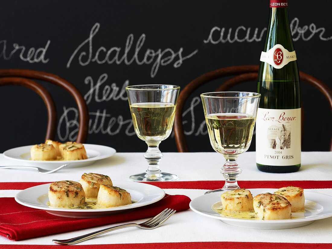 Scallops with herb butter and white wine in front of a blackboard with writing on