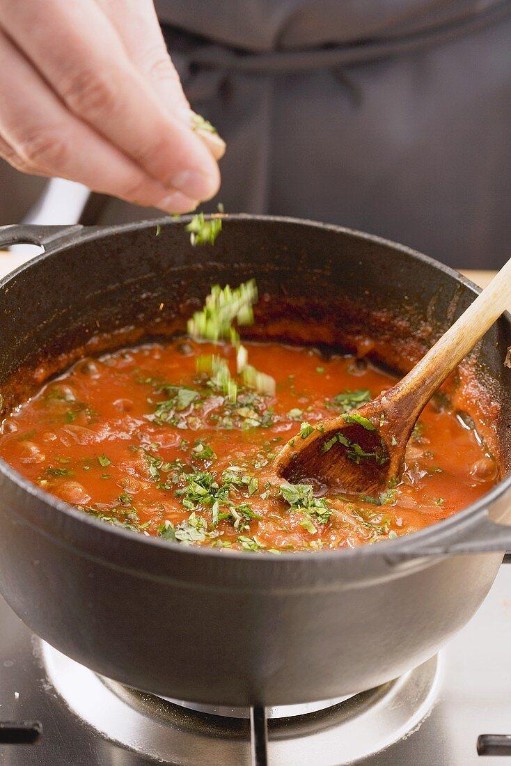 Tomato sauce being seasoned with fresh herbs