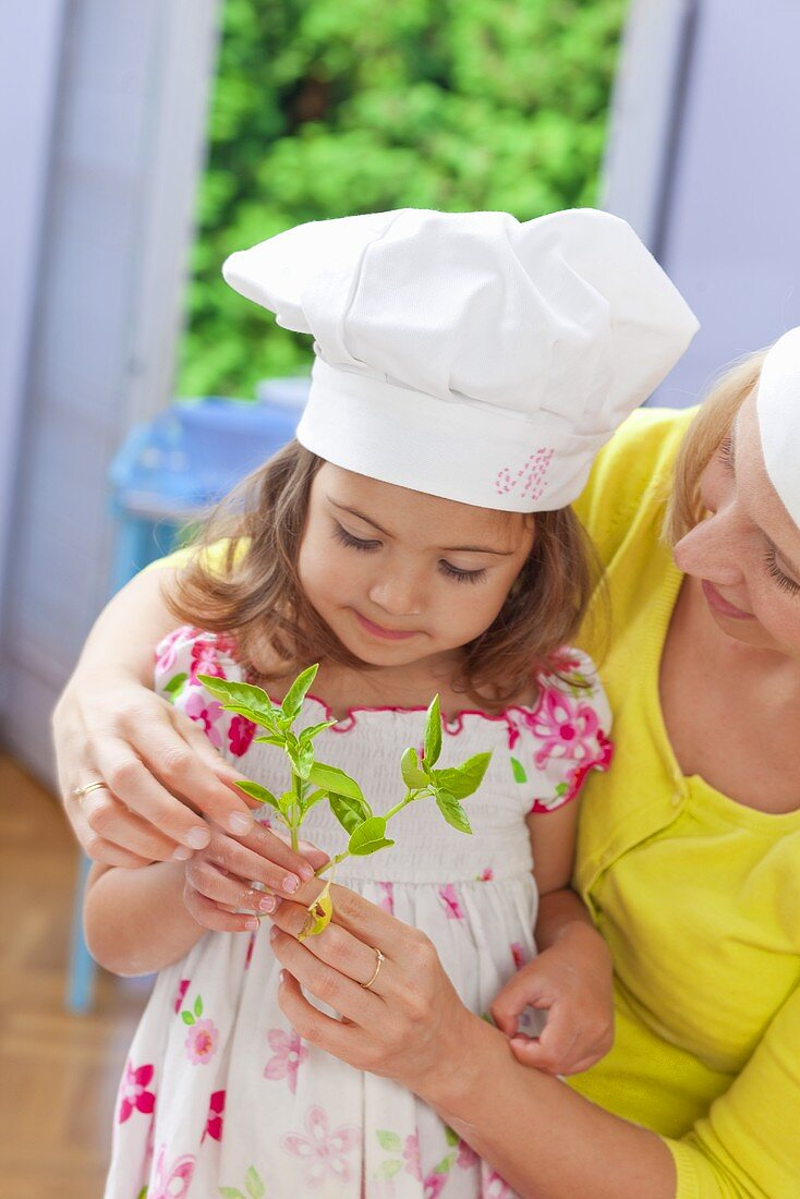 A mother and daughter holding fresh basil