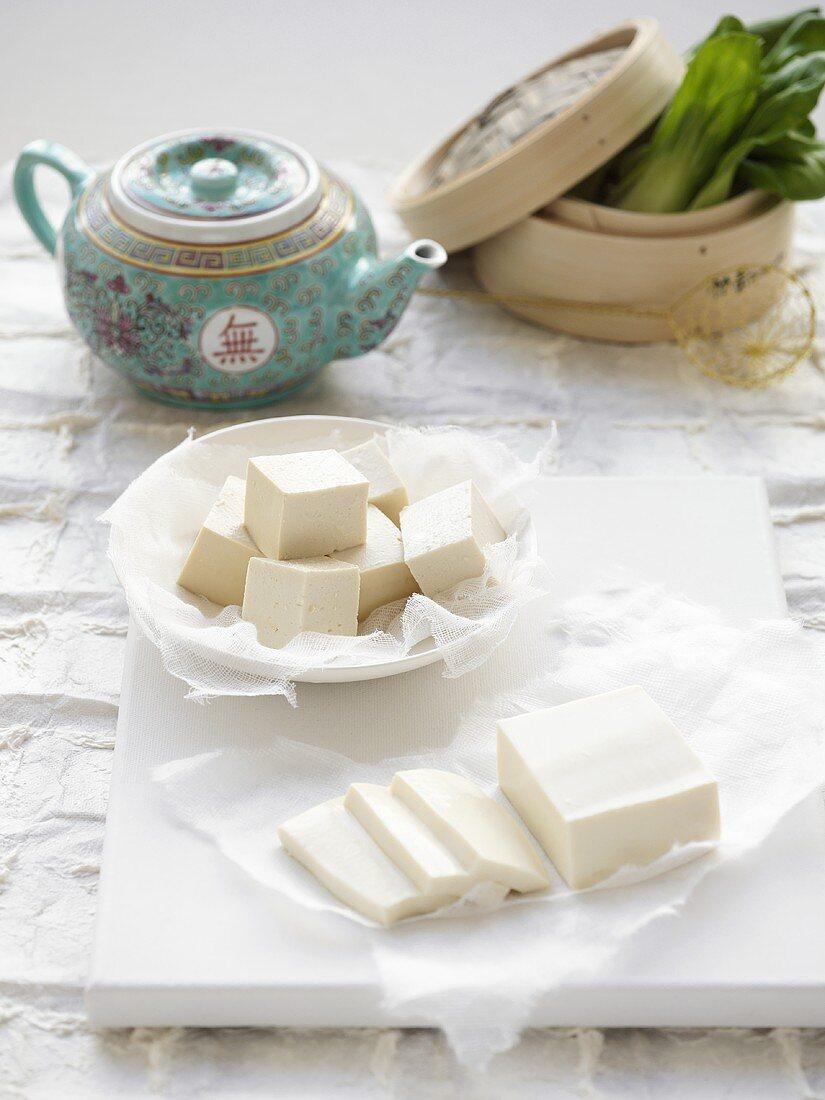 Tofu slices, tofu cubes, tea pot, bamboo steamer with paksoi