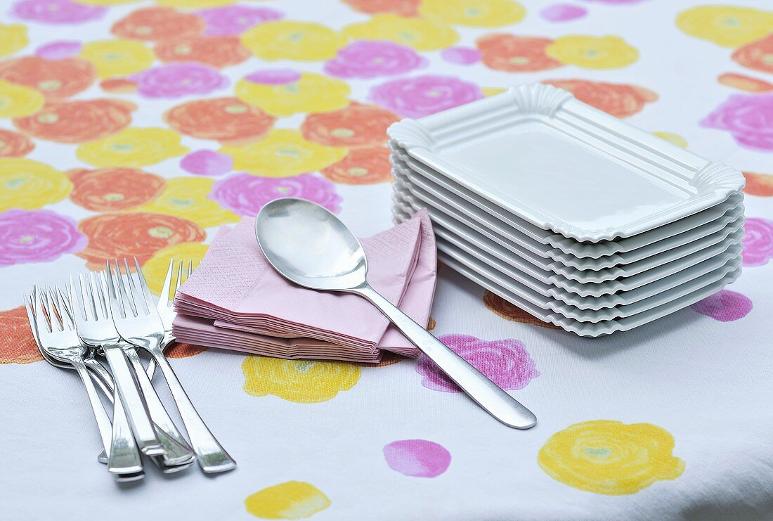 Rectangular plates, spoon, serviettes and fork on a colorful tablecloth
