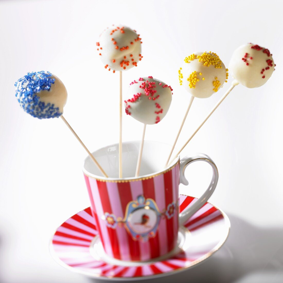 Cake pops with colorful sprinkles in a cup
