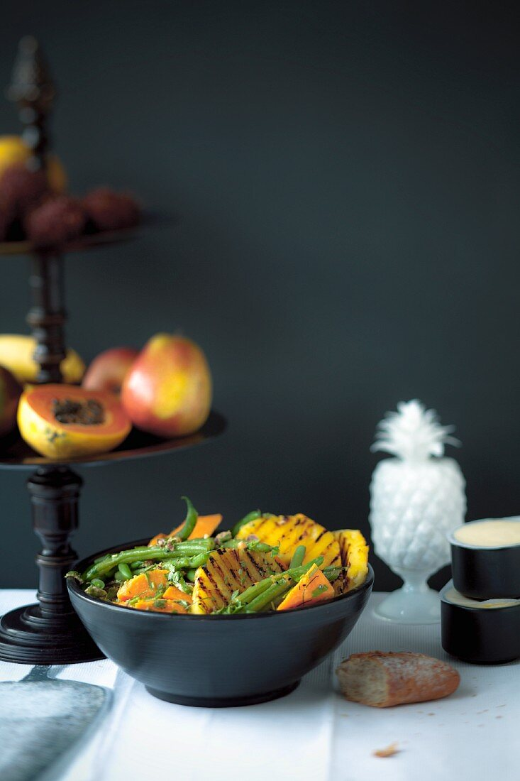 Sweet potato and bean salad with grilled pineapple on a buffet table at a party