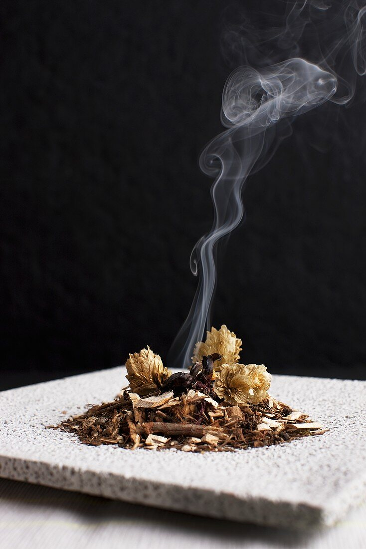 Dried hops flowers and juniper shavings being smoked