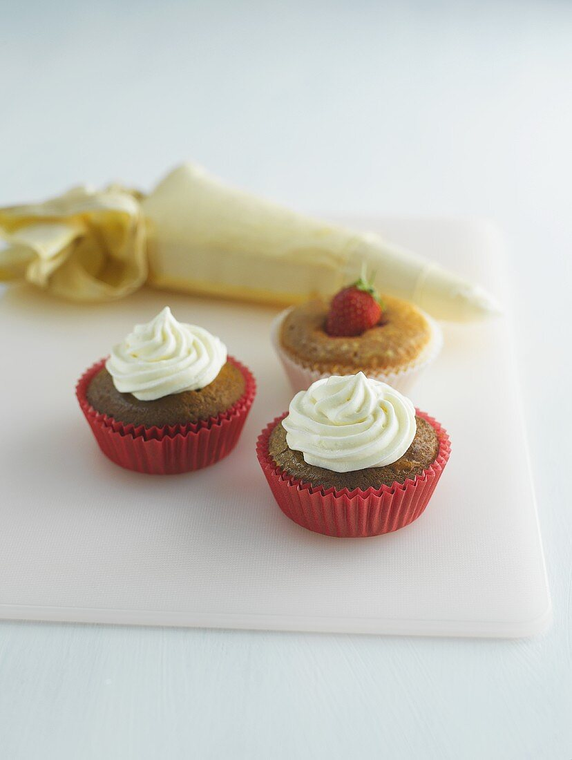 Muffins decorated with cream and strawberries