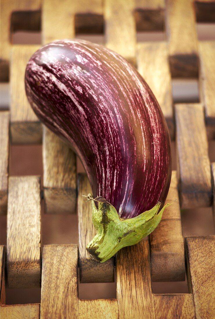 An aubergine on a wooden rack