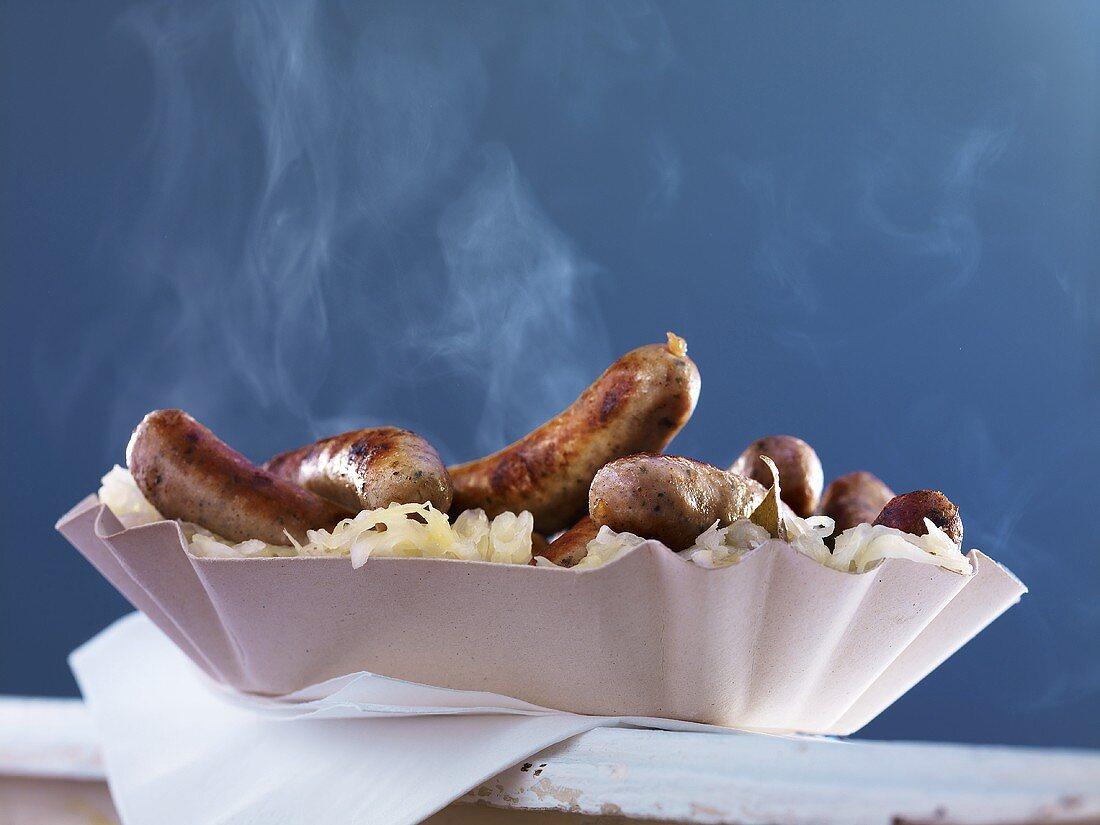 Nuremberg sausages with sauerkraut in a paper plate