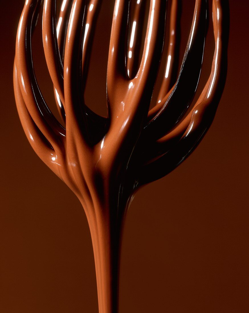 Melted chocolate running off a whisk (close-up)