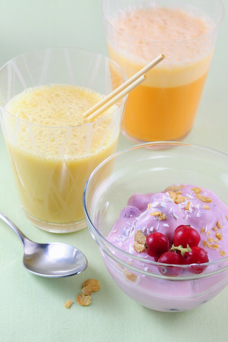 A multivitamin drink, a pear and kefir shake and soya yoghurt with berries