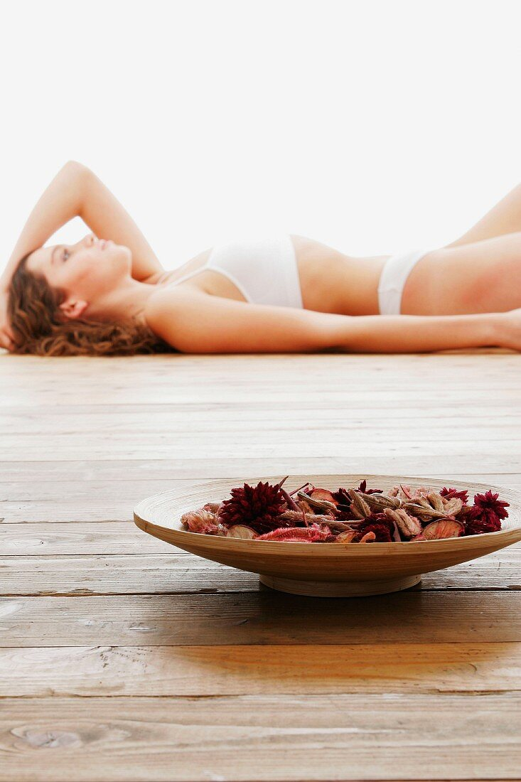 Fragrant potpourri in wooden bowl with woman in underwear in background