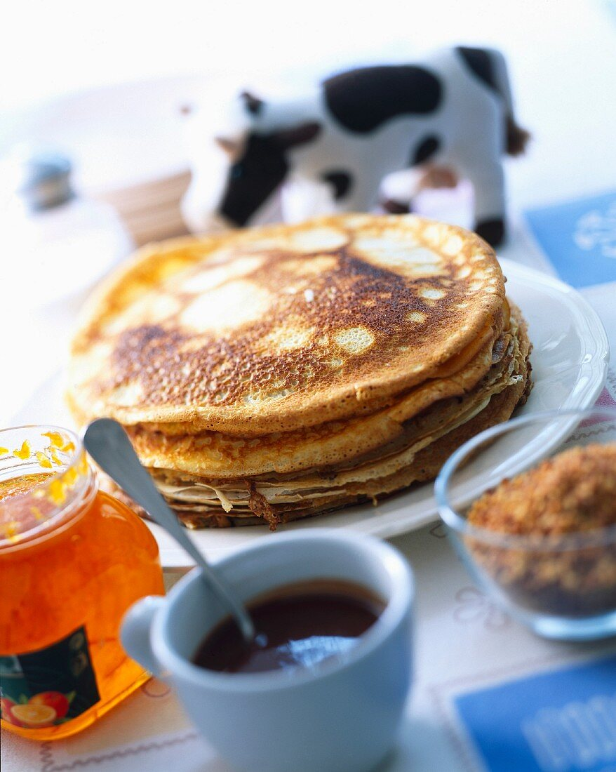 Stacked pancakes with jam and coffee