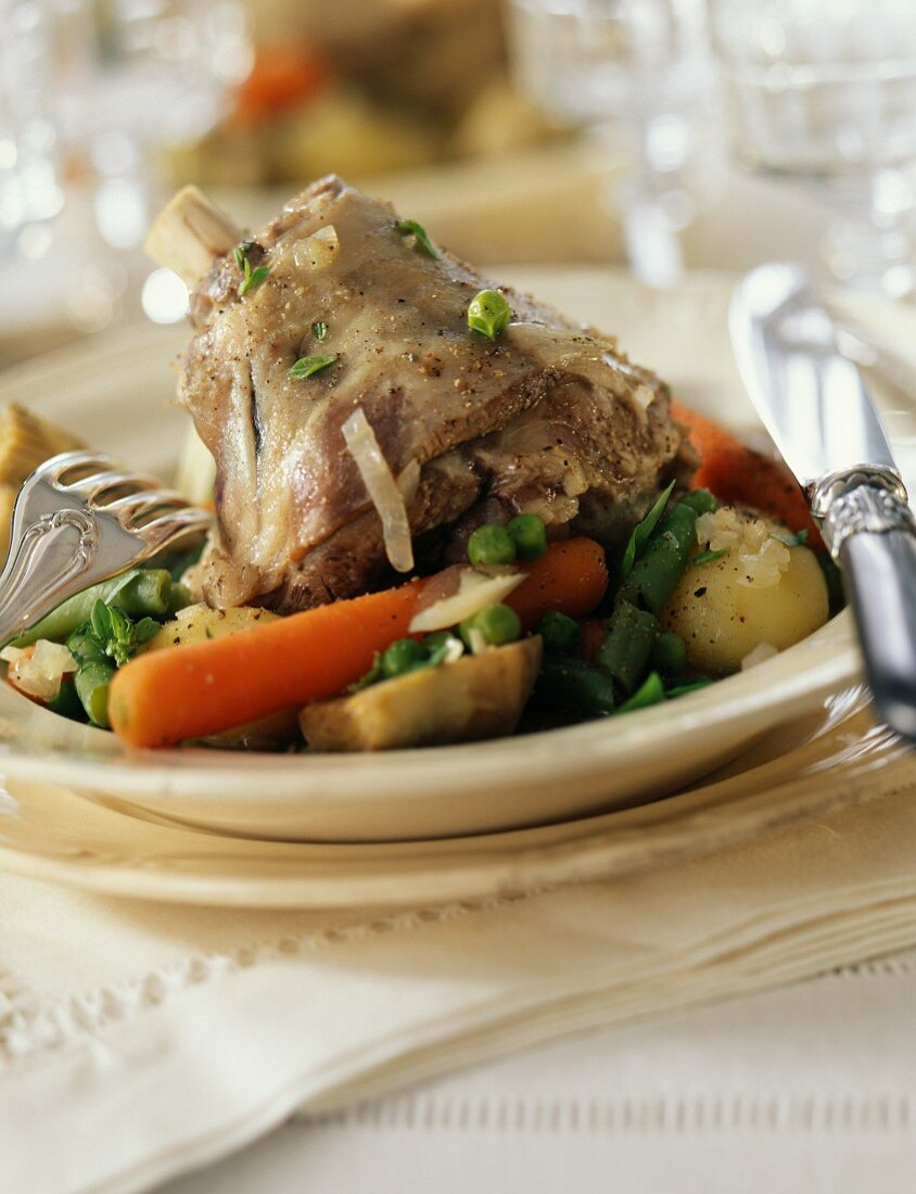 Knuckle of lamb with spring vegetables and artichokes