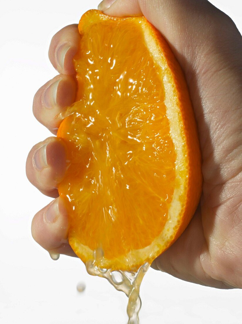 Hand squeezing an orange