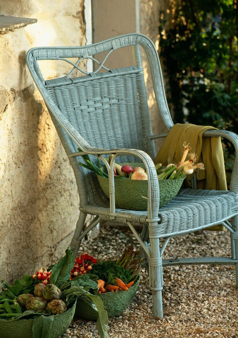 Fresh vegetables on a wicker chair outdoors