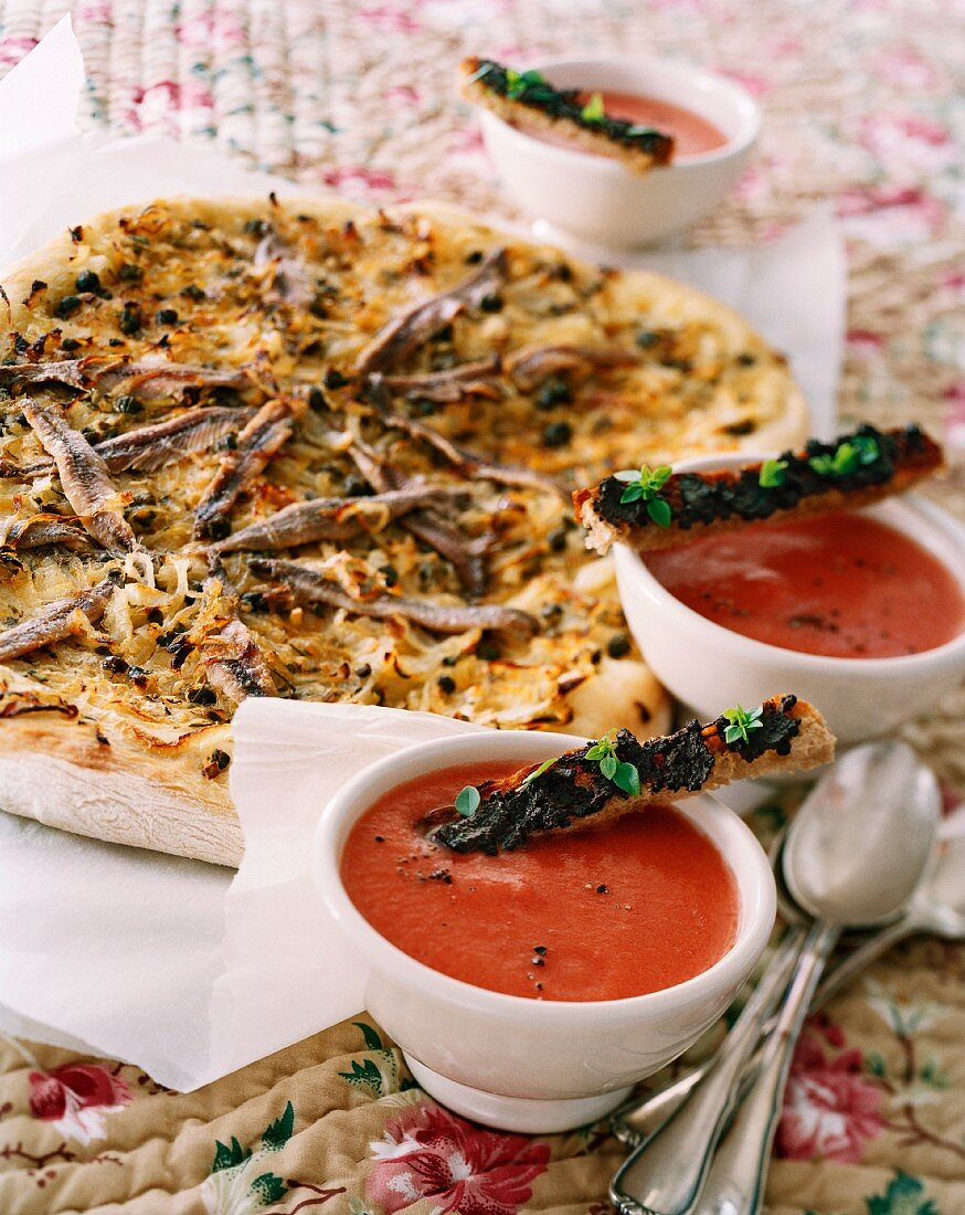 Pissaladière (onion cake with sardine fillets and olives, France) and tomato soup with tapenade bread sticks
