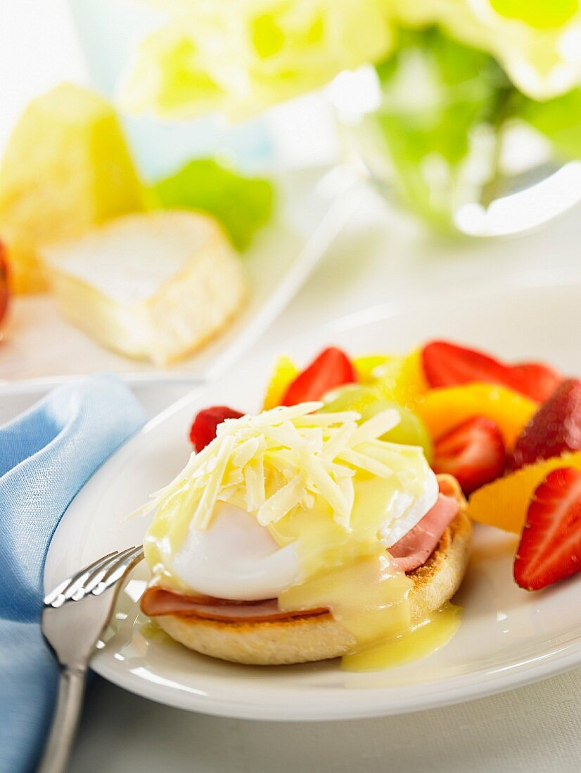 An English muffin with ham, a poached egg and cheese