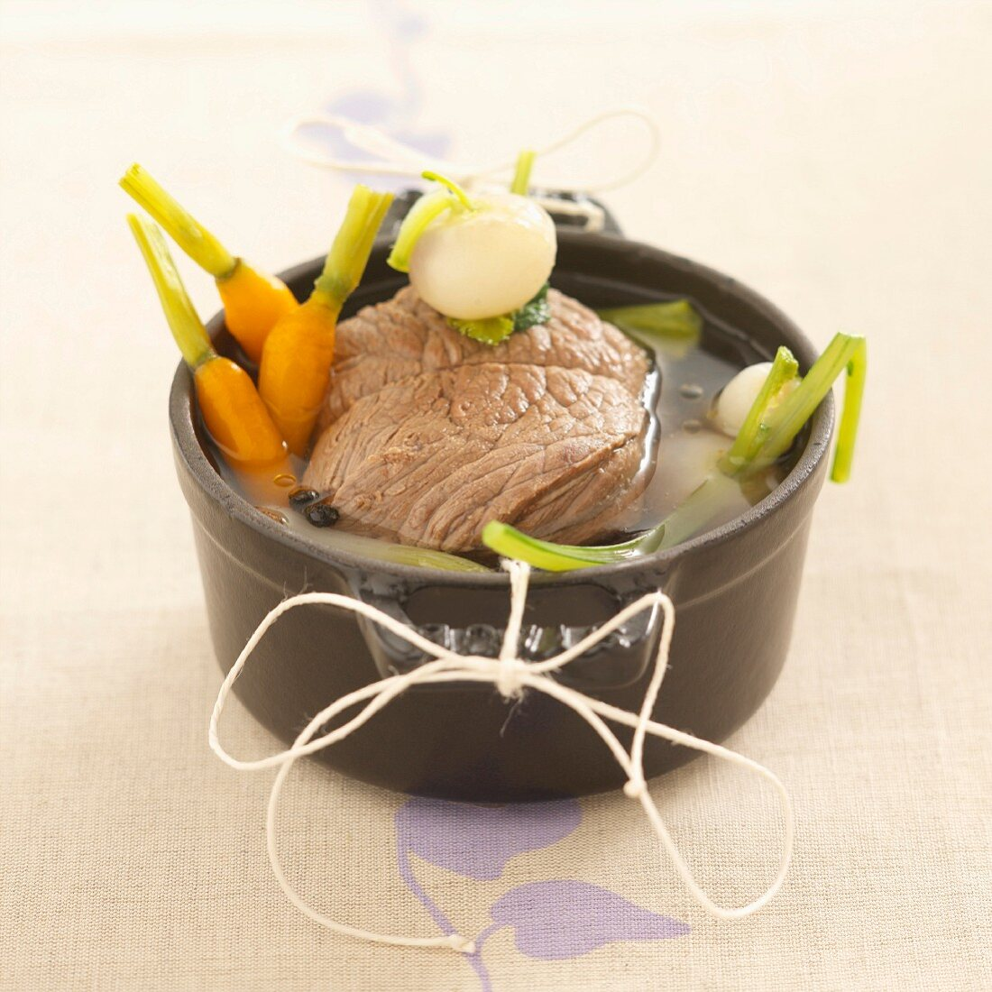 Boiled beef (tied with kitchen twine) with soup vegetables