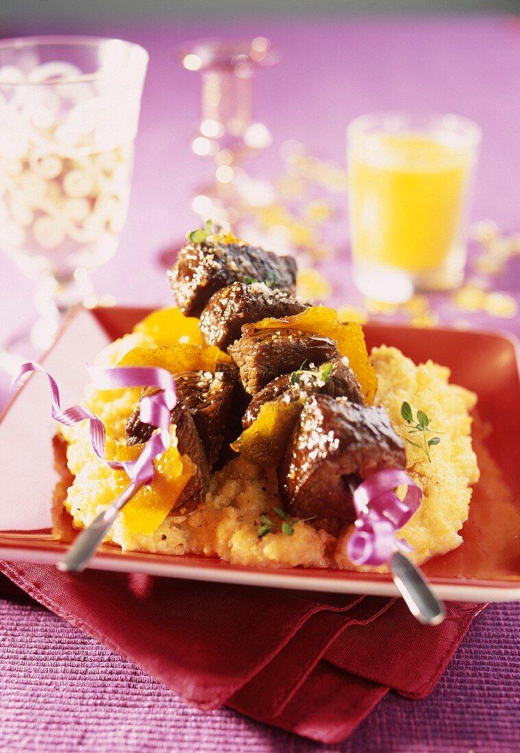 Stag fillet brochettes with almond milk polenta and orange zests