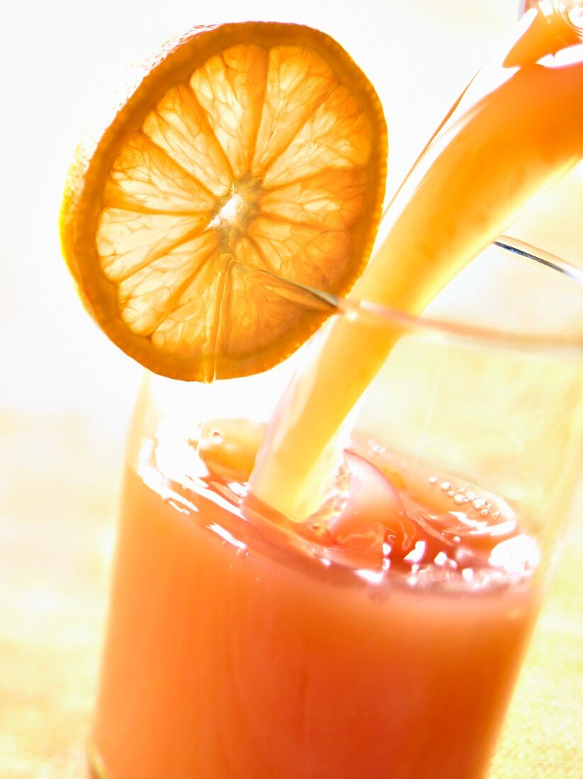 Pouring a mixed pink grapefruit and orange juice