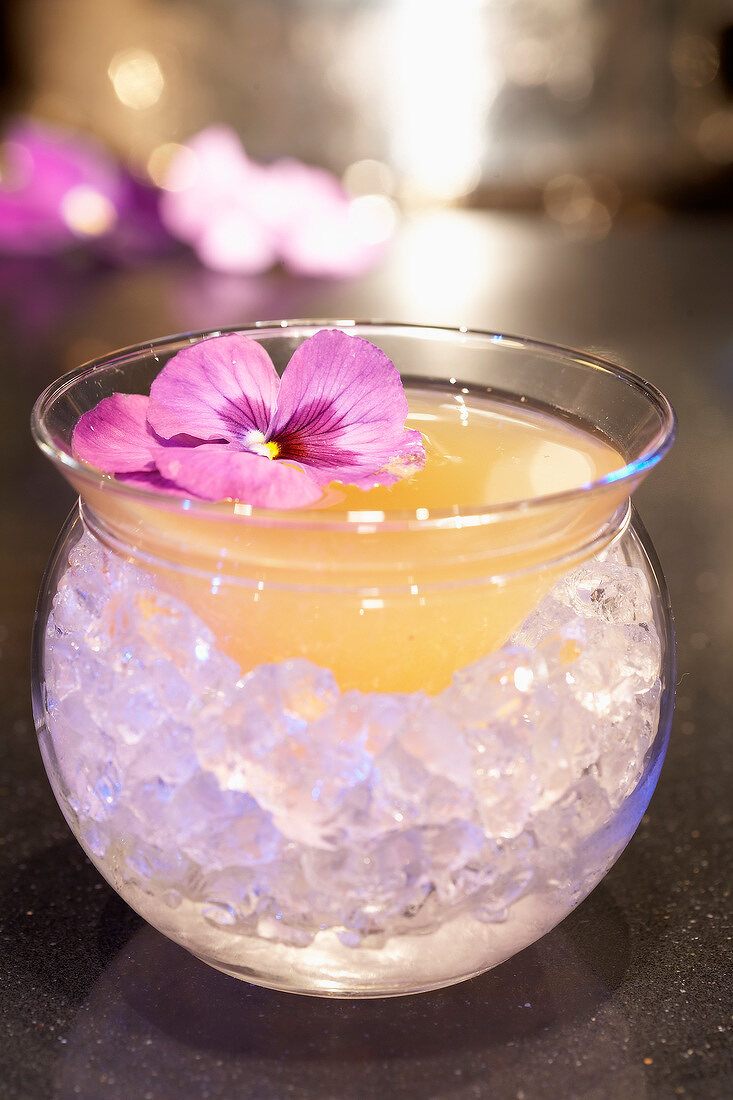 Rum and lime cocktail with a pansy