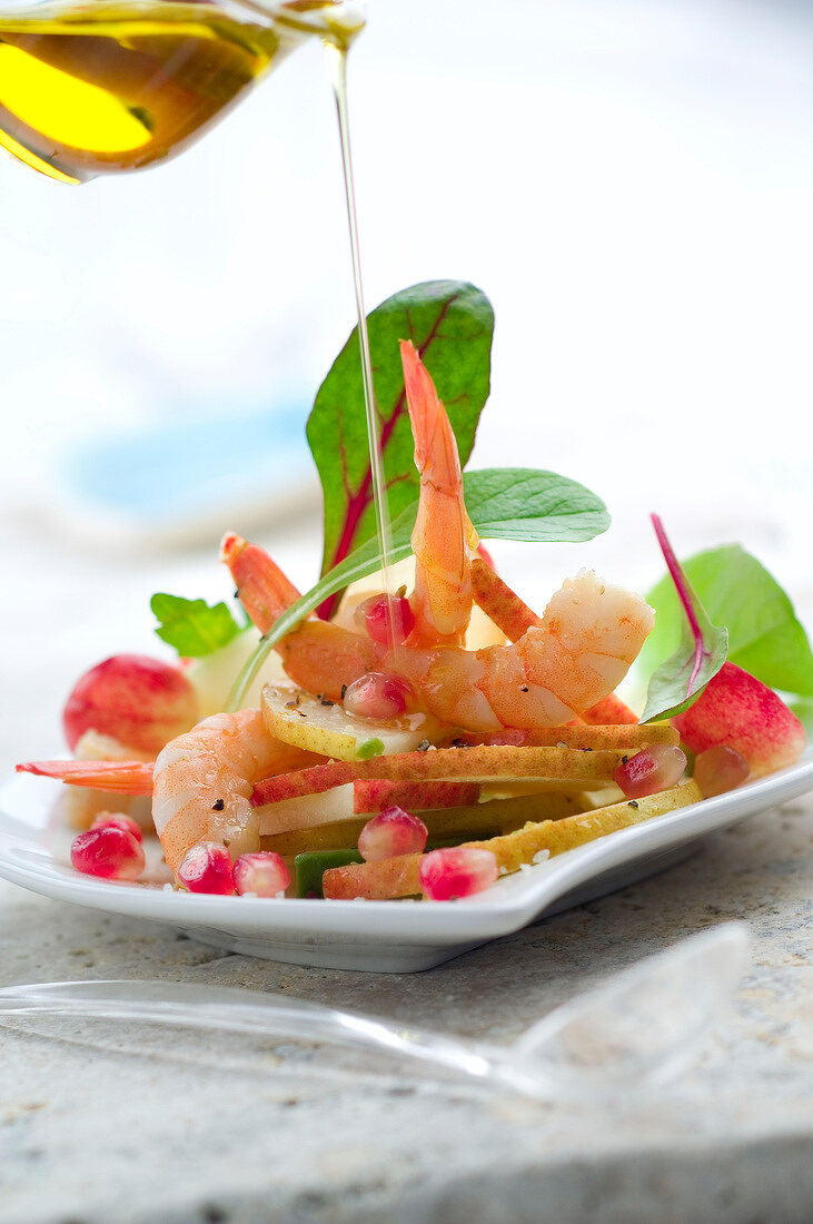 Pouring a drop of olive oil onto the pear and shrimp salad